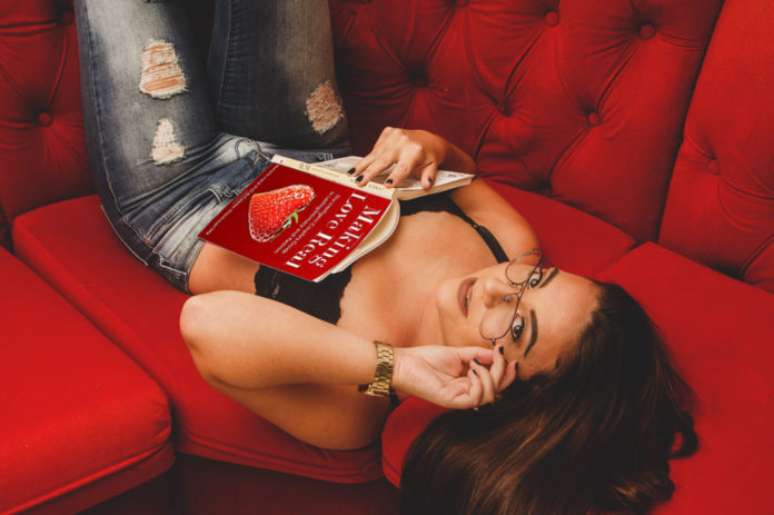 Sex coach reading a book on a red sofa